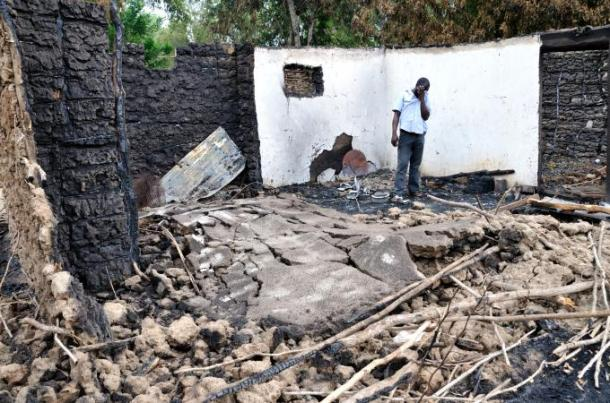 A Pokomo man weeps amid the burned remains of his house [Al Jazeera/Peter Greste]
